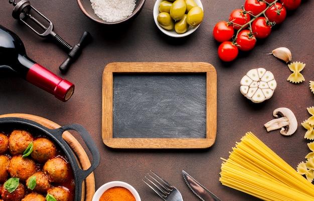 Composizione di piatti italiani piatti con il modello di ardesia Foto Gratuite