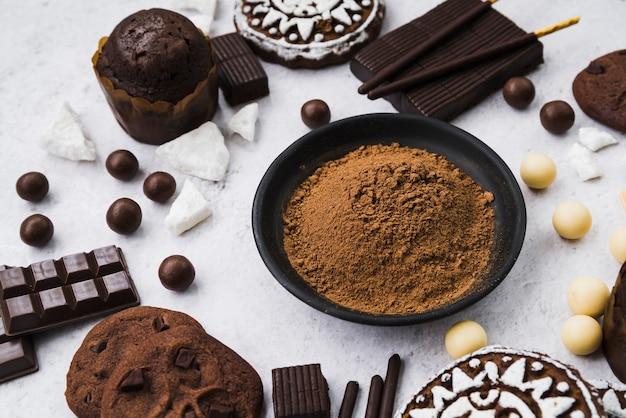 Composizione di prodotti di cioccolato con polvere di cacao Foto Gratuite