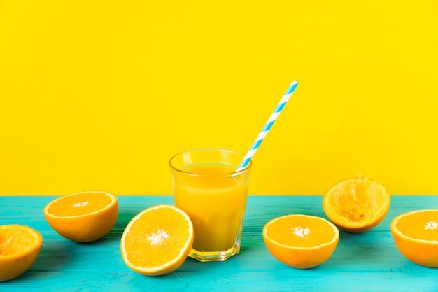 Composizione di succo d'arancia fresco con sfondo giallo Foto Gratuite