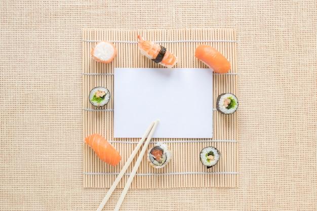 Composizione di sushi piatto laici con modello di carta Foto Gratuite