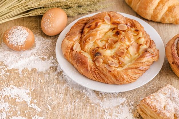 Composizione di una farina di cottura, diversi tipi di pane fresco, grano e uova sulla superficie del tavolo in legno Foto Premium