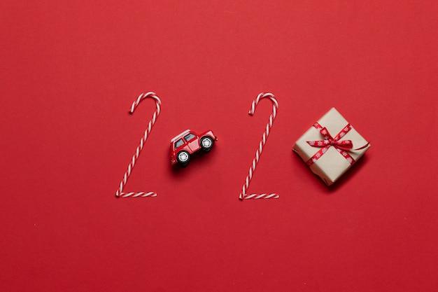 Composizione di vacanze di natale e capodanno 2020 scritte di varie decorazioni auto giocattolo rosso, confezione regalo Foto Premium