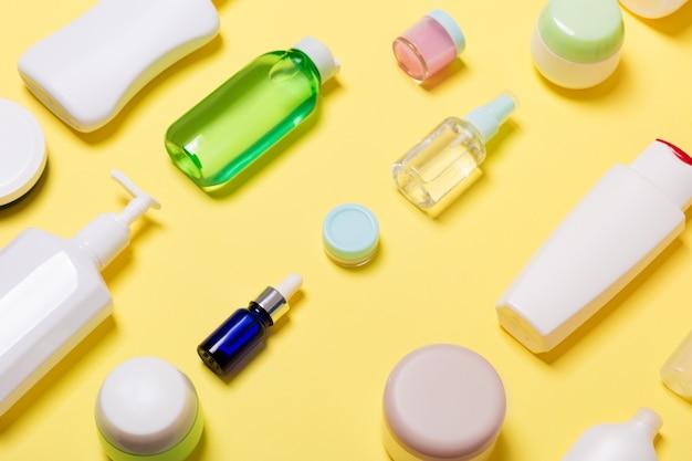 Composizione di vasetti e bottiglie cosmetici di dimensioni diverse su sfondo giallo Foto Premium