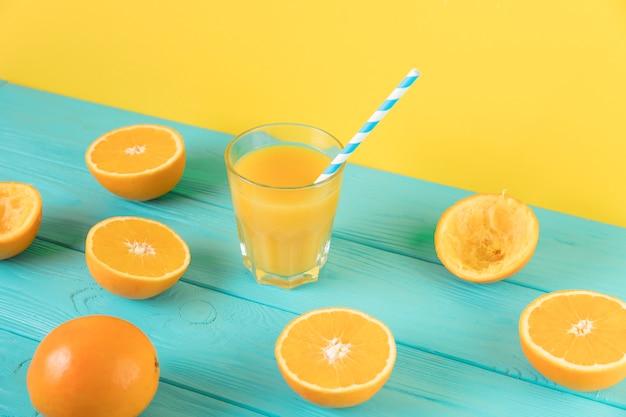 Composizione di vista superiore di succo d'arancia fresco sul tavolo blu Foto Gratuite