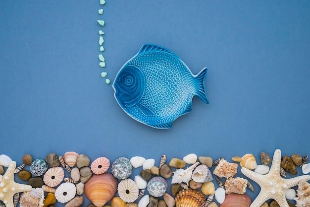 Composizione estiva con pesce blu e varietà di conchiglie Foto Gratuite
