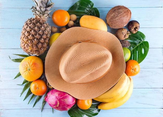 Composizione estiva foglie di palma tropicali, cappello, molti frutti su fondo di legno blu. Foto Premium