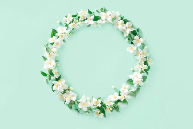 Composizione floreale. corona di fiori di gelsomino bianco primavera su un verde pastello Foto Premium