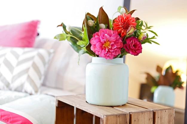 Composizione floreale di fiori rosa in vaso in ceramica bianca sulla scatola di legno Foto Premium