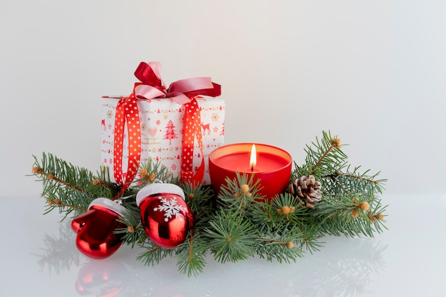 Composizione in natale con decorazioni, scatole regalo, candela rossa, guanti di babbo natale e palline su bianco. vacanze di natale con copyspace. Foto Premium