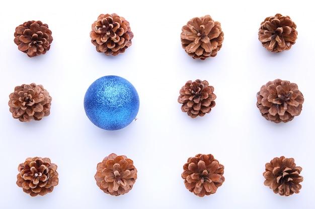 Composizione in natale con le pigne e la sfera blu di natale su priorità bassa bianca Foto Premium