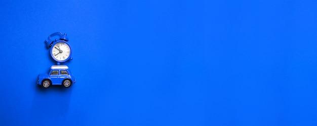 Composizione in tempo di natale con il modello di automobile dei piccoli bambini blu con la sveglia sul cappuccio su un blu Foto Premium