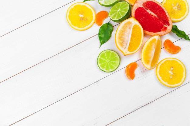 Composizione luminosa di agrumi su fondo di legno bianco Foto Premium