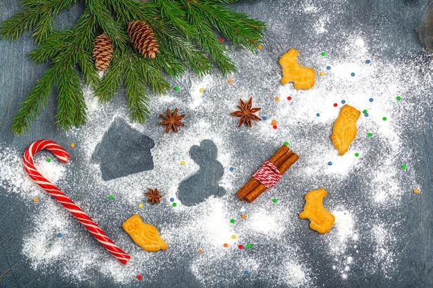 Composizione natalizia piatta. farina silhouette di biscotti su sfondo scuro tra rami di albero di natale, coni, anice stellato, cannella e bastoncino di zucchero. natale, vacanze invernali, concetto di nuovo anno. Foto Premium