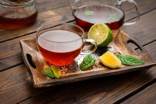 Composizione nell'insieme di tè sulla tavolozza di legno nello stile rustico Foto Premium