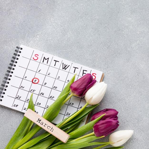 Composizione piana in concetto del giorno delle donne laiche con il calendario Foto Gratuite