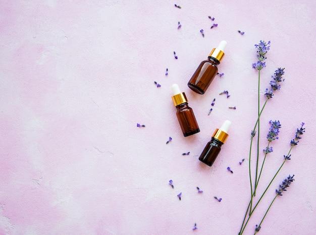 Composizione piatta con fiori di lavanda e cosmetici naturali Foto Premium