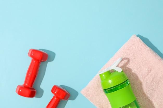 Composizione piatta laica con asciugamano, manubri e bottiglia di fitness su sfondo blu Foto Premium