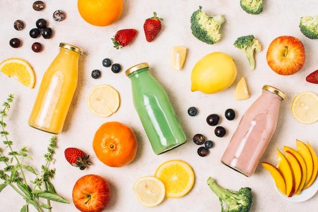 Composizione piatta laici colorati con frullati e frutta Foto Gratuite