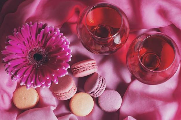 Composizione romantica di fiori, dolci e vino su uno sfondo rosa Foto Premium