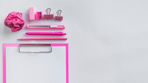Composizione rosa con forniture per ufficio sul tavolo Foto Gratuite