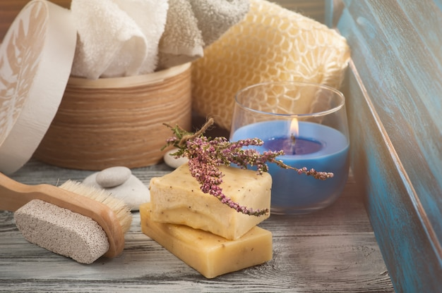 Composizione spa con asciugamani, sapone, pennello, candela accesa Foto Premium