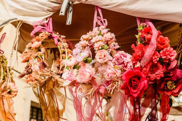Composizioni floreali che pendono da un balcone su una strada in una città mediterranea. Foto Premium