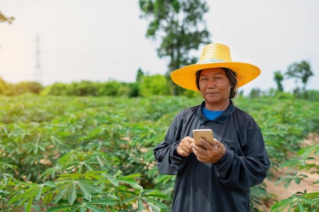 Compressa astuta della tenuta della lavoratrice agricola che sta nel giacimento della manioca per il controllo del suo giacimento della manioca. agricoltura e concetto di successo del coltivatore intelligente Foto Premium