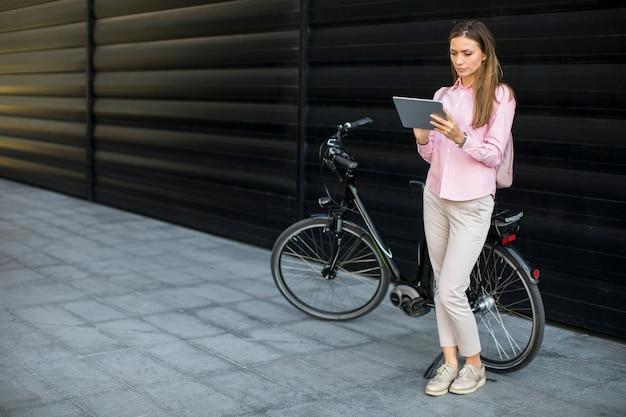 Compressa digitale del witg della giovane donna e bici elettrica all'aperto Foto Premium
