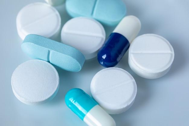 Compresse e pillole bianche e blu su una luce Foto Premium