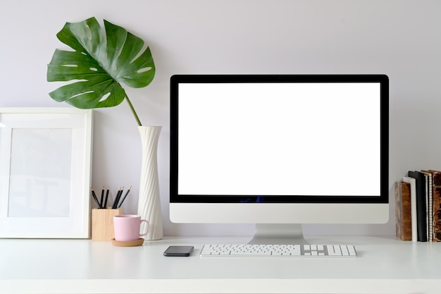 Computer desktop dello schermo in bianco del modello sul tavolo. area di lavoro a casa studio Foto Premium