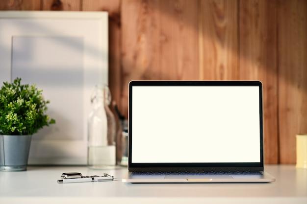 Computer portatile che mostra schermo in bianco su uno scrittorio di legno bianco con un manifesto e gli accessori bianchi Foto Premium