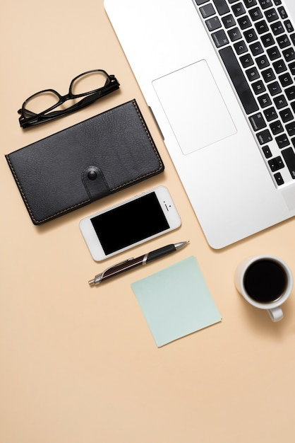 Computer portatile con immagine ritagliata con occhiali; cellulare; tazza di caffè e diario su sfondo beige Foto Gratuite