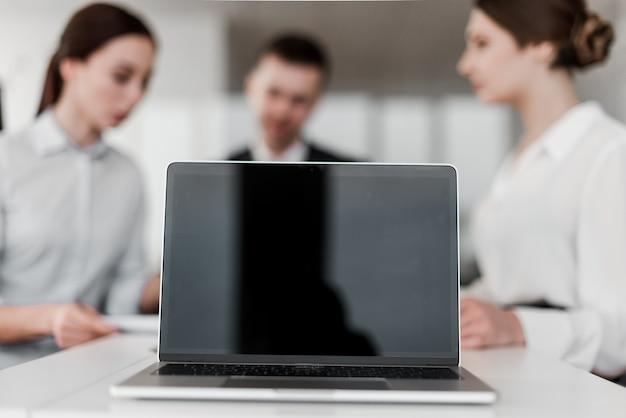 Computer portatile con lo schermo in bianco davanti al gruppo di colleghe Foto Premium