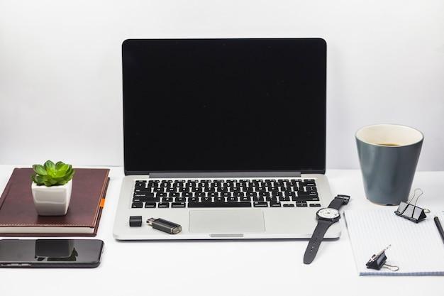 Computer portatile con tazza di caffè e pianta Foto Gratuite