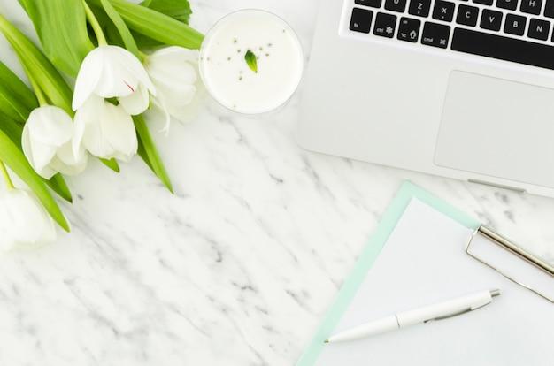Computer portatile con tulipani e appunti sul tavolo luminoso Foto Gratuite
