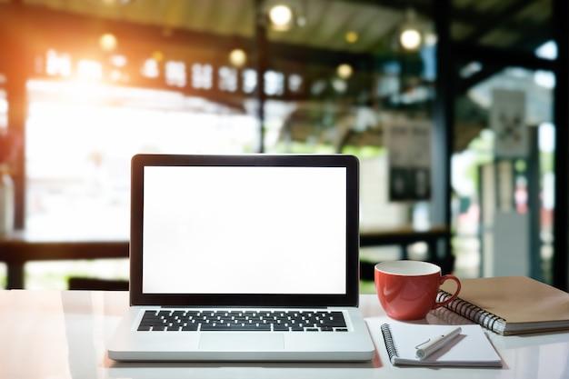 Computer portatile del mockup del computer dell'ufficio con la carta, la penna e la tazza di caffè del blocco note con lo schermo di visualizzazione vuoto. Foto Premium