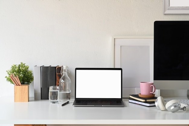 Computer portatile dello schermo in bianco con il manifesto e le forniture per ufficio in bianco. Foto Premium