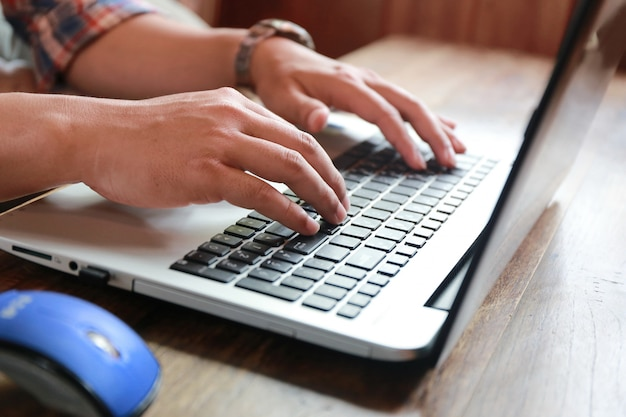 Computer portatile di battitura a macchina dello schermo e dell'uomo commovente delle donne sulla tavola di legno Foto Premium