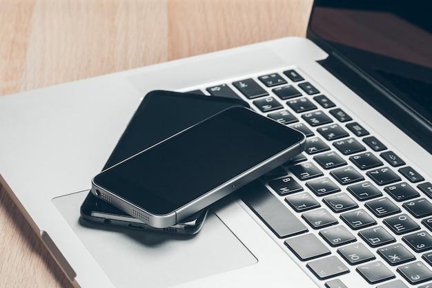 Computer portatile e cellulare sul tavolo. concetto di area di lavoro. Foto Premium