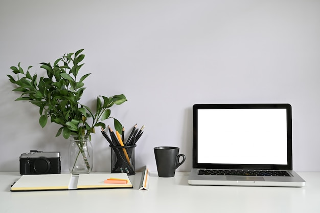 Computer portatile e macchina fotografica del computer dell'area di lavoro con carta del taccuino con caffè. Foto Premium