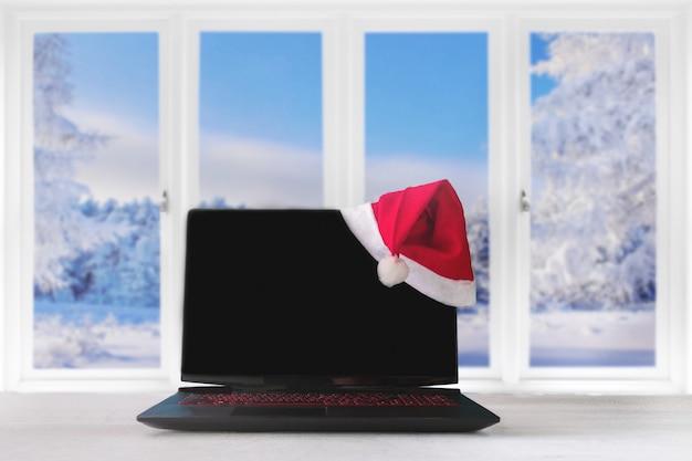 Computer portatile e regali sul tavolo con cappello di babbo natale a casa con una vista panoramica attraverso a Foto Premium