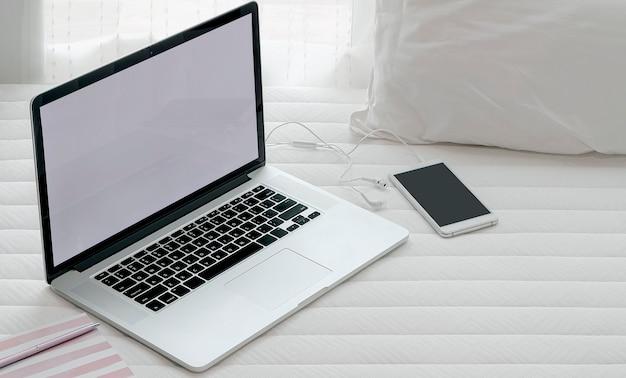 Computer portatile e smartphone sul letto, lavoro dal concetto di casa. Foto Premium