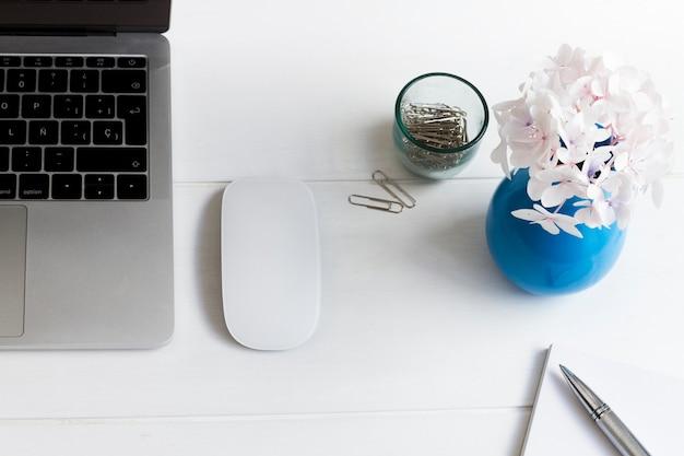 Computer portatile e vaso blu con fiori rosa sulla scrivania sul posto di lavoro Foto Gratuite
