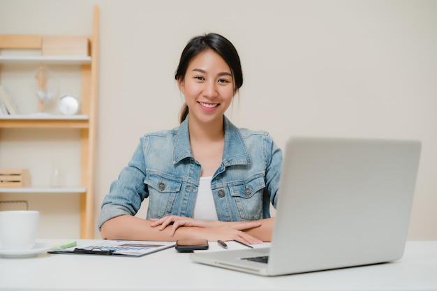 Computer portatile funzionante della bella giovane donna asiatica sorridente sullo scrittorio in salone a casa. Foto Gratuite