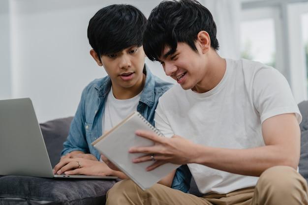 Computer portatile funzionante delle giovani coppie gay asiatiche a casa moderna. l'asia lgbtq + gli uomini si rilassano felici usando il computer e analizzando insieme le loro finanze in internet mentre si trovano il divano nel soggiorno di casa. Foto Gratuite