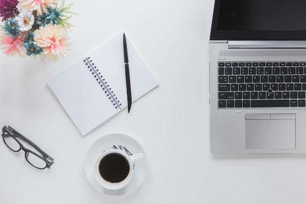 Computer portatile vicino a cancelleria e tazza di caffè Foto Gratuite