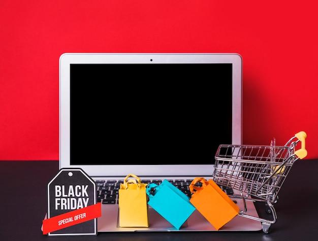 Computer portatile vicino a sacchetti di giocattoli, cartello e carrello del supermercato Foto Gratuite