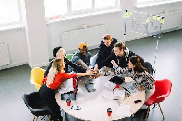Comunicazione di gruppo. vista dall'alto parte di un gruppo di sei giovani in abbigliamento casual discutendo qualcosa con il sorriso, seduti al tavolo dell'ufficio e tenendo le braccia insieme Foto Premium
