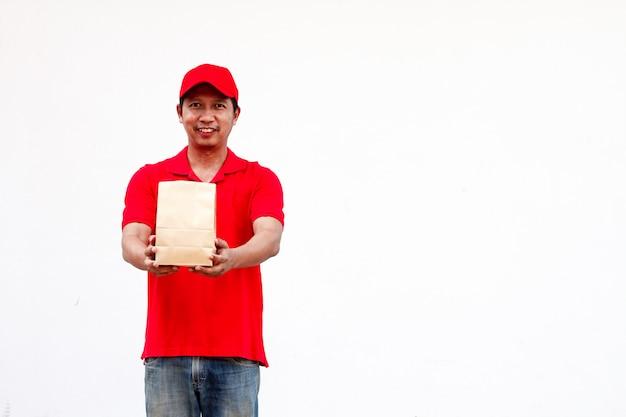 Con in mano vari contenitori per alimenti da asporto, scatola per pizza, supporto e sacchetto di carta, primo piano. sfondo grigio chiaro, posto per inserire il testo. fattorino. Foto Premium