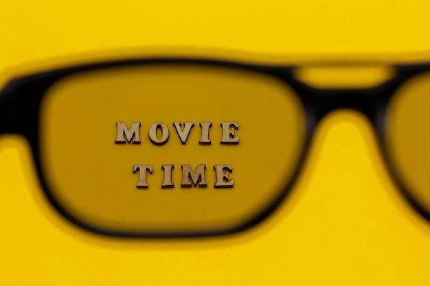 Concentrarsi sul testo tempo del film attraverso occhiali 3d su sfondo di carta gialla. Foto Premium